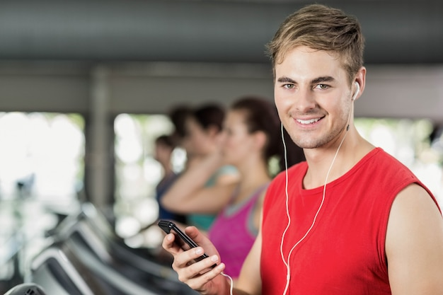 Sorridente uomo muscoloso sul tapis roulant, ascoltando musica in palestra