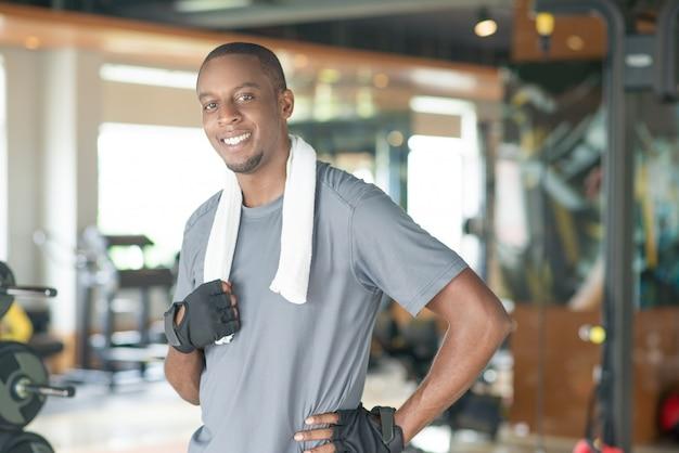 Sorridente uomo nero sportivo che indossa un asciugamano intorno al collo