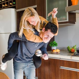 Sorridente uomo portando la moglie sulle spalle giro e divertirsi insieme