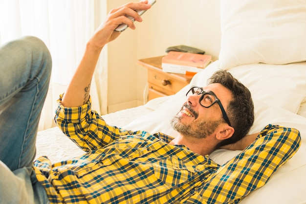 Sorridente uomo sdraiato sul letto guardando il telefono cellulare