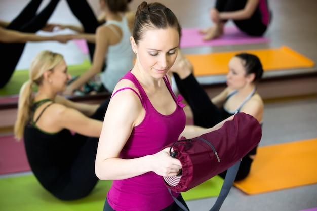 Sorridente yogi ragazza spiegando yoga mat in palestra