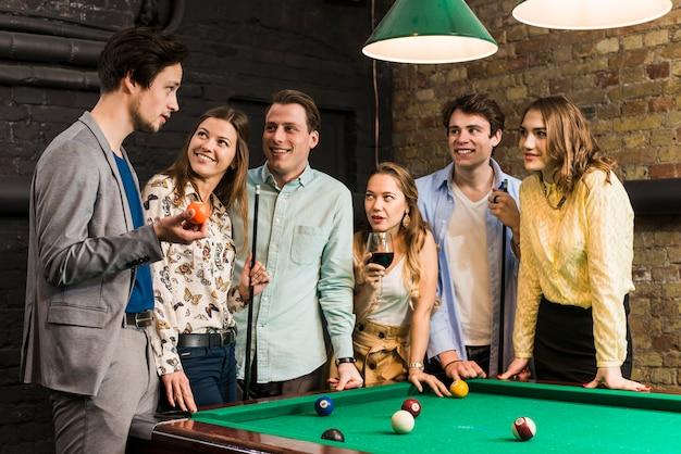 Sorridenti amici maschi e femminili guardando uomo che tiene palla da biliardo nel club