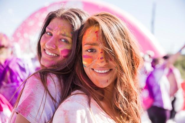 Sorridenti giovani donne con colori holi sul loro viso in piedi schiena contro schiena