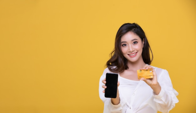Sorridere asiatico bello felice della giovane donna del ritratto allegro e sta tenendo la carta di credito e sta utilizzando lo smart phone per la compera online sul fondo giallo.