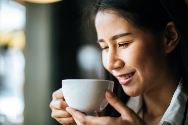 Sorridere asiatico della donna del ritratto si rilassa nel caffè della caffetteria