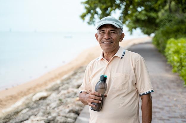 Sorridere asiatico senior maschio con la bottiglia di acqua