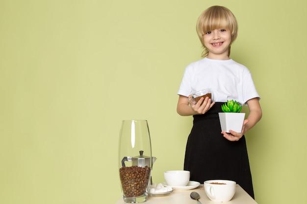 Sorridere biondo di un ragazzo di vista frontale adorabile in polvere bianca del caffè della tenuta della maglietta e piccola pianta verde sullo spazio colorato pietra
