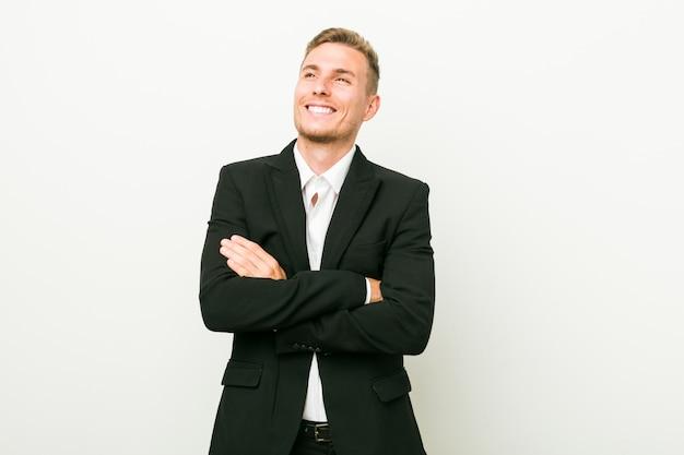 Sorridere caucasico giovane dell'uomo di affari sicuro con le braccia attraversate.