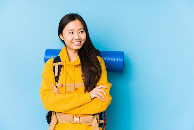 Sorridere cinese giovane della donna di viaggiatore con zaino e sacco a pelo sicuro con le armi attraversate.
