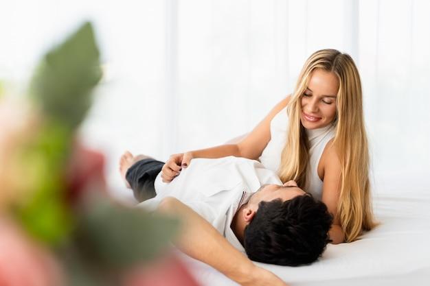 Sorridere delle coppie soddisfatto dell'amante sul letto nella mattina