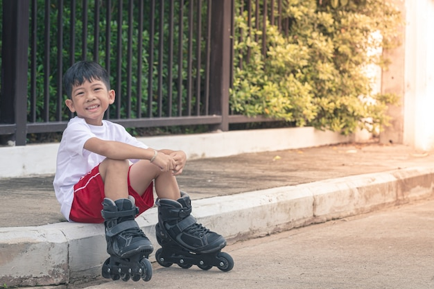 Sorridere di seduta dell'asia del ragazzo alle scarpe di rollerblade