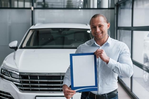 Sorridere e avere buon umore. il manager si trova di fronte alla moderna automobile bianca con carta e documenti in mano