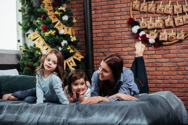 Sorridere e divertirsi. generi e due bambini che si sdraiano sul letto con stanza che ha decorato con l'albero di natale