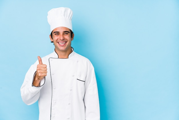 Sorridere e sollevare isolati uomo del cuoco dei giovani su