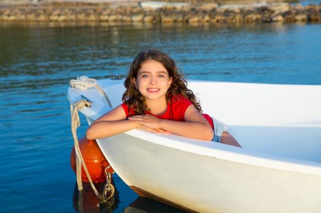 Sorridere felice della ragazza del bambino del marinaio rilassato nell'arco della barca