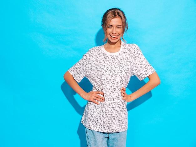 Sorridere femminile positivo modello divertente che posa vicino alla parete blu in studio. mostra la lingua e sbatte le palpebre