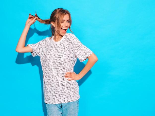 Sorridere femminile positivo modello divertente che posa vicino alla parete blu in studio