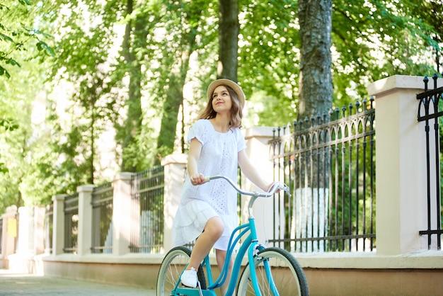 Sorridere godente sorridente della giovane donna allegra che cicla al parco locale che guarda intorno