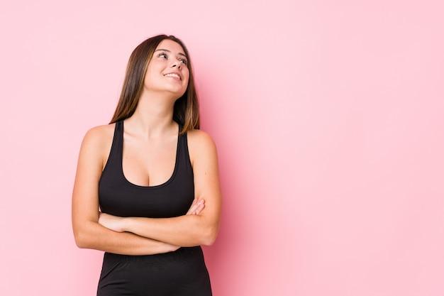 Sorridere isolato donna caucasica di giovane forma fisica sicuro con le braccia attraversate