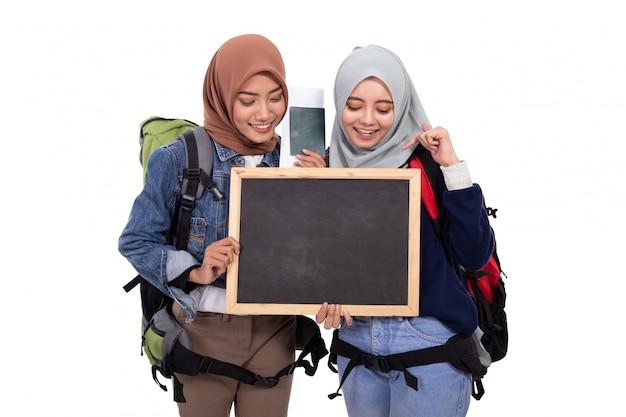 Sorridere musulmano felice di viaggiatore con zaino e sacco a pelo isolato sopra fondo bianco
