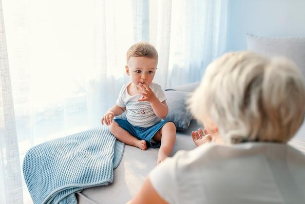 Sorridere sveglio del piccolo della tenuta senior della donna. felice nonna con il suo nipotino in casa.