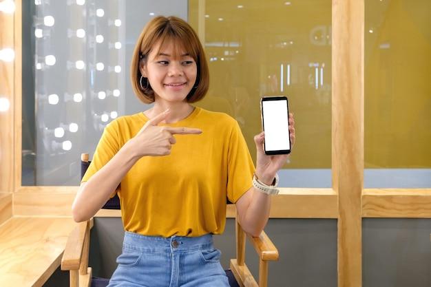 Sorridi la donna asiatica che guarda e che tiene lo smartphone con lo schermo in bianco
