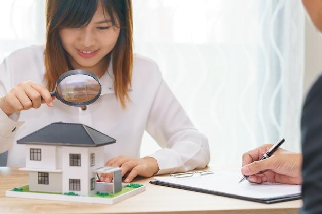 Sorridi la donna che cerca la nuova casa o che ispeziona le case prima dell'acquisto con l'uomo di vendita