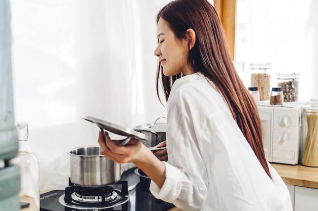 Sorridi la donna che sta e che cucina dalla stufa e dal vaso per preparare l'ingrediente per la cottura dell'alimento nella cucina a casa