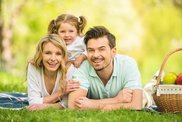 Sorridi padre e madre. famiglia avendo picnic all'aperto.