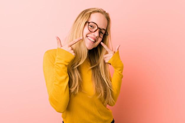 Sorrisi adorabili della donna dell'adolescente, indicanti le dita alla bocca.