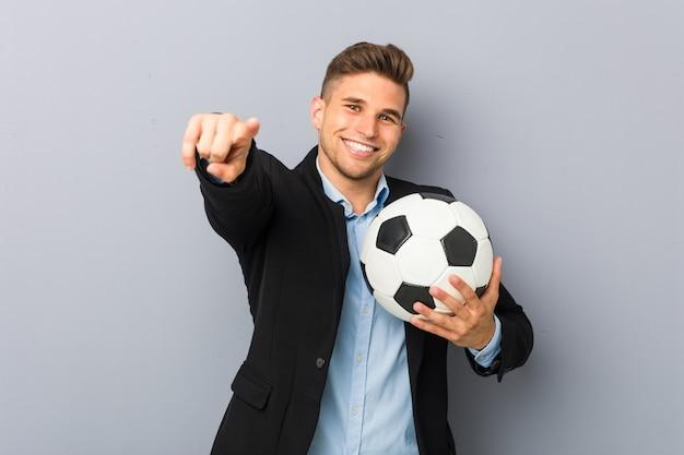 Sorrisi allegri del giovane istruttore di calcio che indicano la parte anteriore.