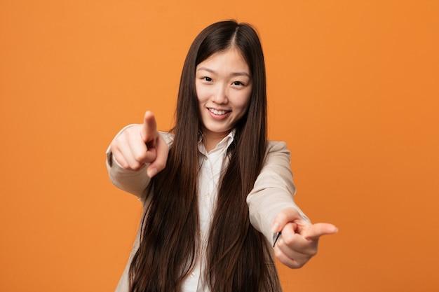 Sorrisi allegri della donna cinese di giovani affari che indicano la parte anteriore.