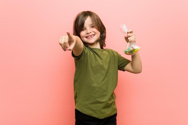 Sorrisi allegri delle caramelle caucasiche della tenuta del ragazzino che indicano la parte anteriore.