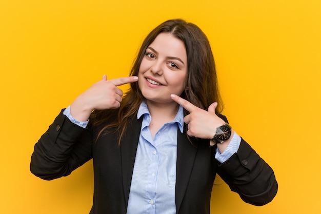 Sorrisi della donna di affari caucasica plus size giovani, che punta le dita alla bocca.