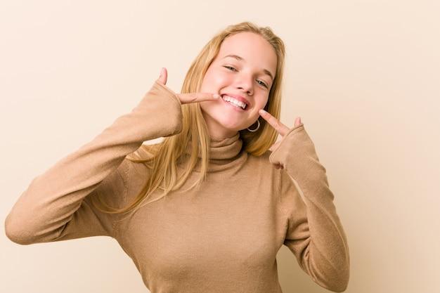 Sorrisi di donna adolescente carino e naturale, puntando le dita alla bocca.
