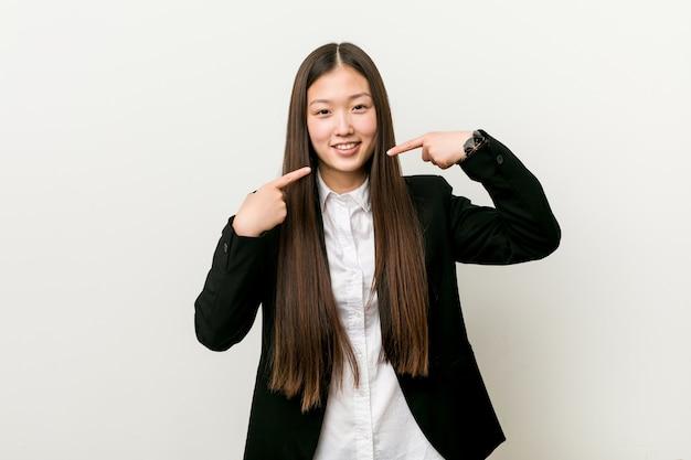 Sorrisi di donna d'affari piuttosto giovane cinese, che punta le dita alla bocca.