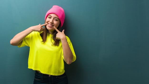 Sorrisi di giovane donna moderna, indicando la bocca