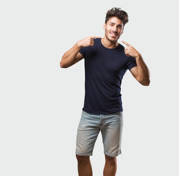 Sorrisi di giovane uomo bello in piedi, che indica la bocca, concetto di denti perfetti, denti bianchi, ha un atteggiamento allegro e gioviale