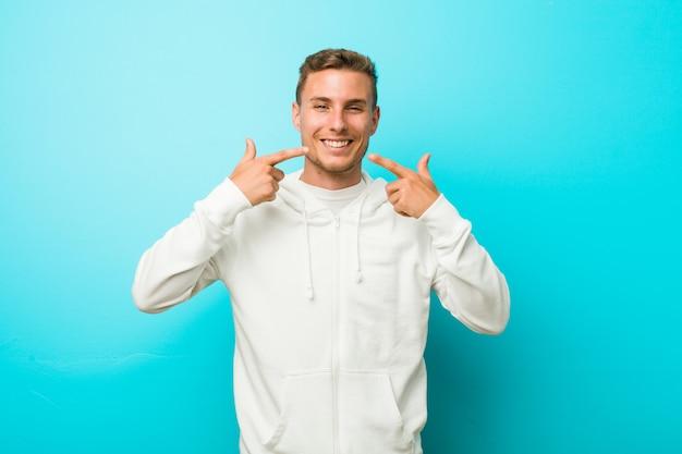 Sorrisi di giovane uomo caucasico sport, puntando le dita alla bocca.