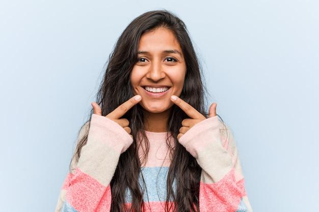 Sorrisi indiani di moda giovane donna, puntando le dita alla bocca