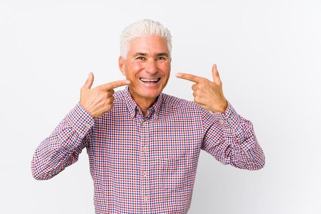 Sorrisi senior dell'uomo caucasico, indicando le dita alla bocca.