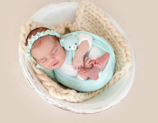 Sorriso affascinante del giocattolo che abbraccia neonato addormentato