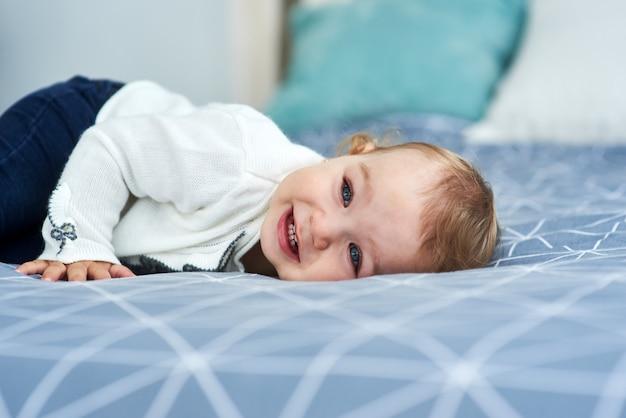 Sorriso amichevole della neonata che si trova sul letto