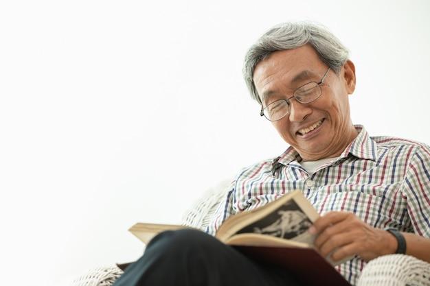 Sorriso anziano asiatico mentre seduto a leggere nella stanza bianca