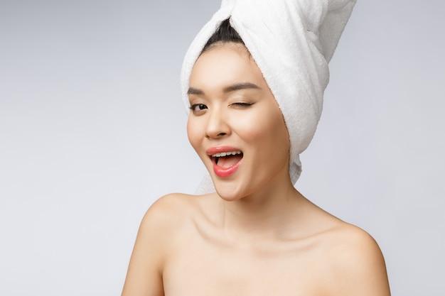 Sorriso asiatico della giovane donna con i denti bianchi, ritenenti così felicità ed allegro