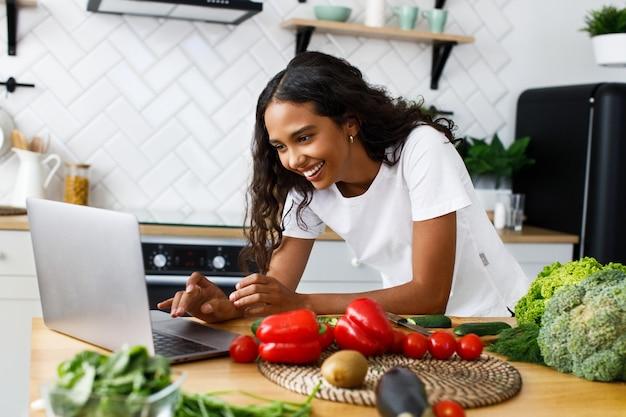 Sorriso bella mulatta sta guardando sullo schermo del computer portatile sulla cucina moderna sul tavolo pieno di frutta e verdura, vestito con una maglietta bianca