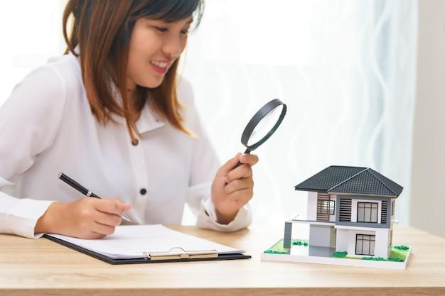 Sorriso donna alla ricerca di una nuova casa o ispezionare le case prima di acquistare il concetto.