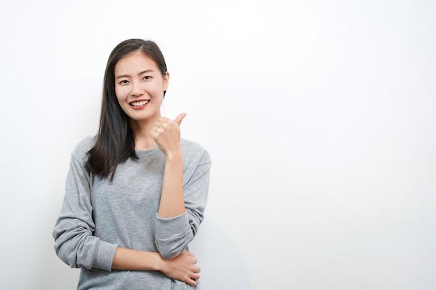 Sorriso e pollice asiatici svegli della donna in su. concetto felice e positivo