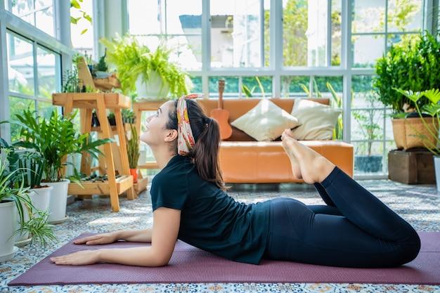 Sorriso felice bella giovane donna asiatica che allunga allenamento di esercizio a casa