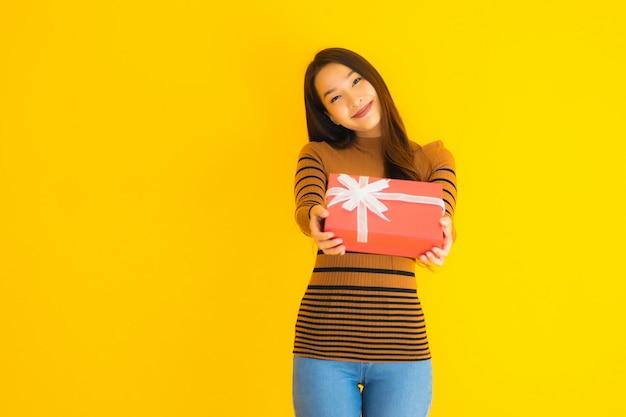 Sorriso felice della bella giovane donna asiatica del ritratto con il contenitore di regalo rosso sulla parete gialla